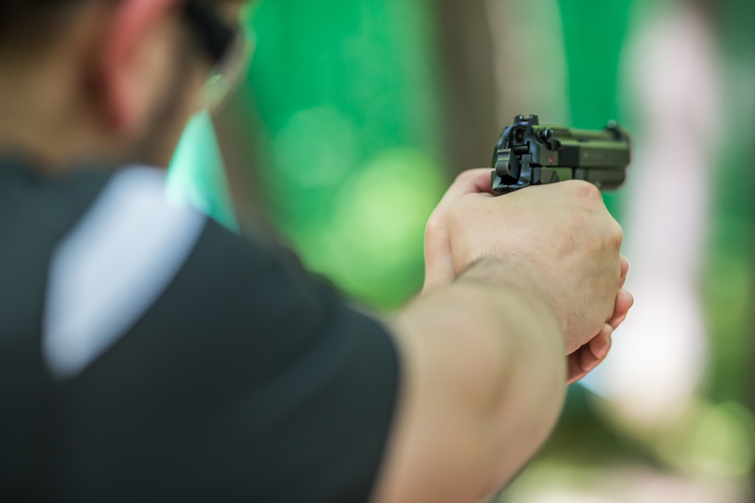 Man practicing shooting with a handgun at the shooting range
