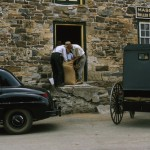 An Amish buggy and a Mennonite car parked in front of a flour mill.