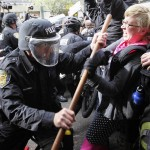 A Seattle police officer wearing riot gear tangles with a woman during May Day demonstrations that went violent in downtown Seattle