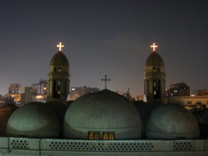 three-domed Coptic church with crosses on top lit up at night