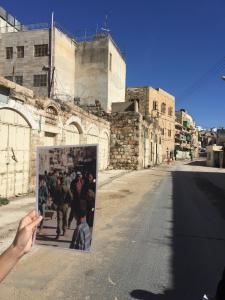Our guide holds up a picture of this street in Hebron before the Israeli occupation. You can see the deserted street that exists now.