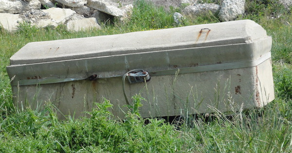 A stone casket at Anchor of Hope Cemetery. The cemetery has suffered from significant erosion.