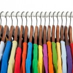 Multicolored clothes on wooden hangers