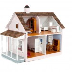Furnished pink doll house on white