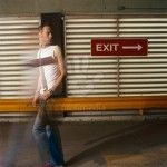 Man walking away from exit sign
