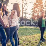 stock-photo-19541267-excluded-sad-girls-is-looking-the-group-talking