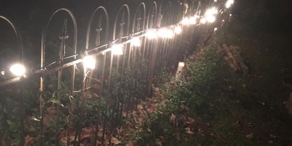 Cemetery Fence with Sanctuary Candles lit for all the Ancestors of the Land, buried there. ~Heron Michelle