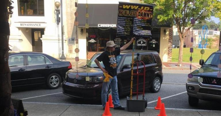 """EC Street Preacher"" witnessing outside of The Sojourner with his ""Who Would Jesus Damn?"" sign, August 26, 2017. Photo Credit: Heron Michelle"
