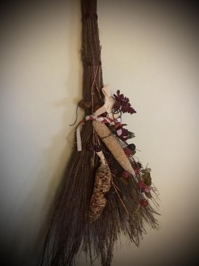 This cinnamon broom hangs beside my altar, with the mementos of Sabbats past: A corn dolly, belled ribbon anklet, hazelnut charm, dried corn cobs, etc. I add and subtract from it regularly.