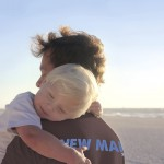 Young Child Resting in Father's Arms on Beach